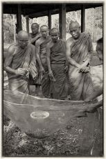 The monks wash the ash from the cremated remains one by one